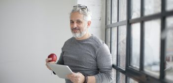 smiling-middle-aged-man-using-tablet-and-holding-apple-near-3931603